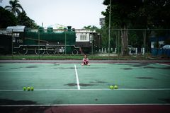 Portrait Asian girl sits on the tennis court after playing hard stock photography