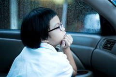 Portrait Asian girl sitting in car and looking out of window watching the rain. stock photography