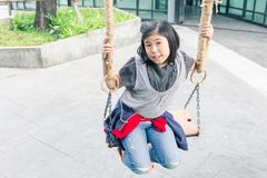 Portrait asian girl sitting on chain swing Royalty Free Stock Photos