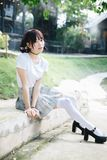 Portrait of asian girl with white shirt and skirt sitting and smile in outdoor nature vintage film style stock photography