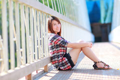 Portrait of the asian girl 20 years old posing outdoors wear plaid shirt. Sitting on white bridge ,park view in the afternoon in warm color tone Stock Photography