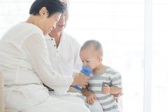 Grandparents babysitting grandchild. Portrait of Asian grandparents feeding water to grandchild at home, family indoor lifestyle Stock Images