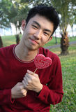 Portrait of asian guy with lollipop Stock Photo