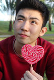 Portrait of asian guy with lollipop Royalty Free Stock Images