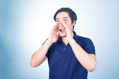 Portrait of Asian guy yelling, screaming, shouting, hand on his Royalty Free Stock Photo