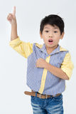 Portrait of asian happy boy pointing away and looking at camera Royalty Free Stock Images