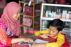 Portrait of asian hijab muslim mother explaining what inside magazine to son royalty free stock photography