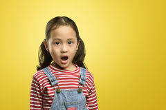 Portrait of asian kid with funny shocked face expression. Against yellow background royalty free stock photo