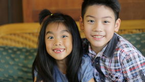 Portrait of asian kids, happy asian boy and girl looking at camera and smiling. stock video