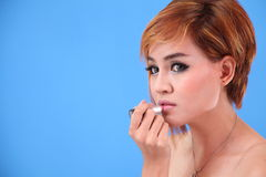 Portrait of Asian lady applying lipstick Royalty Free Stock Images