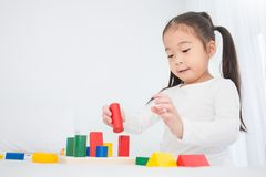 Portrait of asian little cute girl playing colorful blocks on white background royalty free stock photo