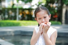 Portrait of Asian little girl eating bread with Stuffed Strawberry-filled dessert and Stained around her mouth in garden outdoor stock photos