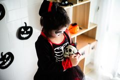 Portrait Asian little girl in Halloween costume holding the skull royalty free stock image