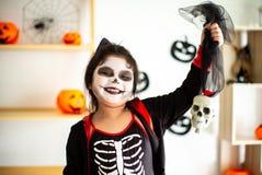 Portrait Asian little girl in Halloween costume holding the skull royalty free stock photos