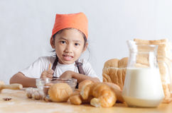 Portrait of Asian little girl holding dough in hand and bakery o Stock Image