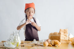 Portrait of Asian little girl holding dough in hand with copy sp Royalty Free Stock Image