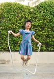 Portrait of asian little girl jumping handmade rope among swing in the park. Selective focus royalty free stock photos