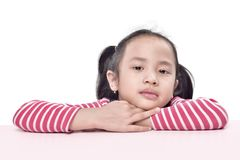 Portrait of asian little girl lean back on the table. Posing isolated over white background Stock Image