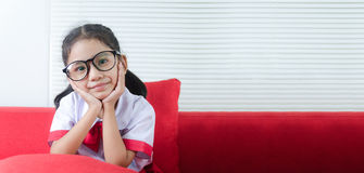 Portrait of Asian little girl in Thai student unifom sitting chi Royalty Free Stock Photo