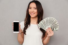 Portrait of asian lucky woman 20s holding fan of money dollar ba. Nknotes and demonstrating copyspace screen of cell phone over gray background royalty free stock photos