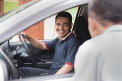 Man talking to car driver. Portrait of asian male car driver talking to someone from his car window Royalty Free Stock Photos
