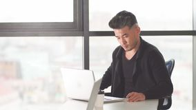 Portrait of Asian male lawyer at his desk in the office looking at his personal computer.  stock video