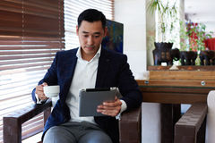 Portrait of an Asian man intelligent lawyer reading electronic book on touch pad during coffee break in cafe, Royalty Free Stock Photography