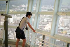 Portrait Asian man looking the city view from the high tower, Beppu tower, in Japan. Attractive place for tourism stock photo