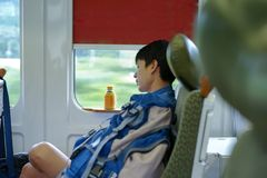 Portrait Asian man napping during traveling by train. royalty free stock photo