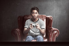 Portrait of asian man playing video games Stock Images