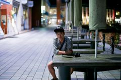 Portrait of Asian man sits on the wooden bench and looks at the camera royalty free stock photo