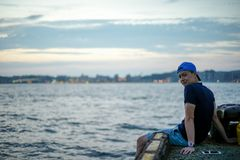 Portrait Asian man sitting on the port and looking out to the sea with the twilight sky of sunset and bokeh lights of the city in. Background stock photos