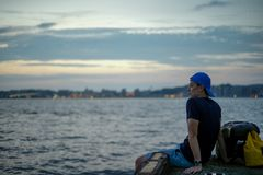 Portrait Asian man sitting on the port and looking out to the sea with the twilight sky of sunset and bokeh lights of the city in. Background stock photo