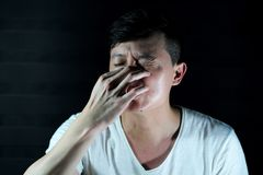 Portrait Asian man squeezes his nose by his finger. S. Avoid stinky odor by closing nose royalty free stock images