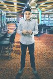 Asian man with mobile phone in the casino Royalty Free Stock Image