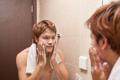 Portrait of an asian man washing in bathroom.  Royalty Free Stock Photography
