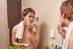 Portrait of an asian man washing in bathroom.  Stock Image
