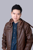 Portrait of asian man wearing jeans shirt amd jacket. Portrait of asian man wearing jeans shirt and leather jacket, close up shot on white background Royalty Free Stock Photography