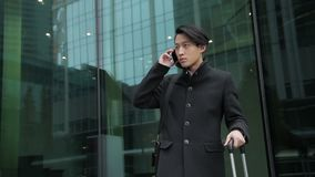 The portrait of asian man, who stands near the modern airport and calls on his smartphone. stock footage