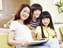 Portrait of asian mother and children. Asian mother and two children sitting on couch reading a book stock images