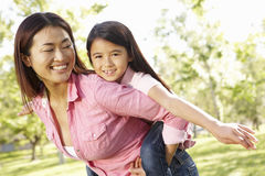 Portrait Asian mother and daughter playing in park Stock Images