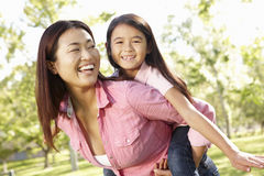 Portrait Asian mother and daughter playing in park Stock Photo