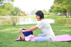 Portrait of Asian mother doing baby yoga for her son on green lawn in the nature garden outdoor stock photography
