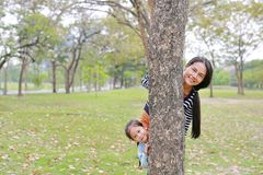 Portrait of Asian mother and little child girl hide body behind tree trunk in summer garden outdoor royalty free stock image