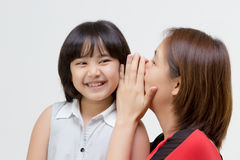 Portrait of Asian mother whispering to her daughter. On isolated royalty free stock photography
