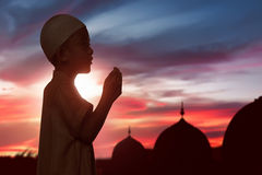 Portrait of asian muslim child raising hand and praying. Over sunset background Royalty Free Stock Image