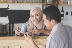 Female waitress showing the menu to her customer. Portrait of asian muslim female waitress showing cafe menu to her cutomer Stock Photos