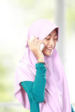 Portrait of an asian muslim kid talking on the cell phone Royalty Free Stock Photography