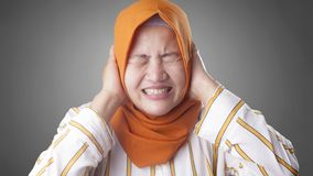 Asian Muslim Lady Close Her Ears. Portrait of Asian muslim lady wearing hijab close hear ears with hands as if do not want to hear something bad indonesian stock photo