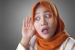 Muslim Lady in Listening Carefully, Hand on Ear. Portrait of Asian muslim lady wearing hijab hold her hand on ear trying to listening carefully to the royalty free stock images